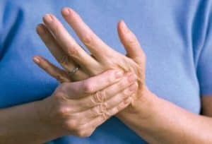 A man rubbing his hand to relieve nerve pain